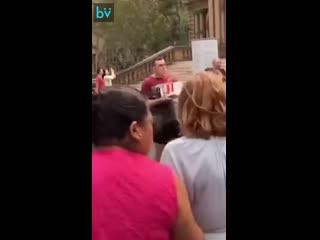 Парень с аппетитом уплетает курочку рядом с протестующими веганами