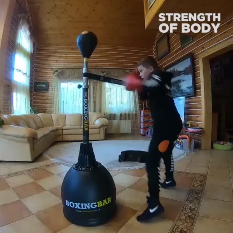 Юный боксер тренируется дома на тренажере