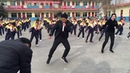 School pupils do choreographed shuffle dance with principal during break
